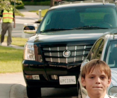 Kevin Costner with Cadillac Escalade SUV in Black or White