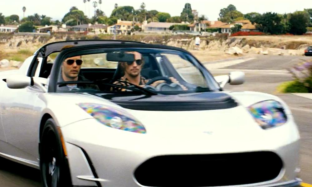 Taylor Kitsch with Tesla Roadster Sport in Savages